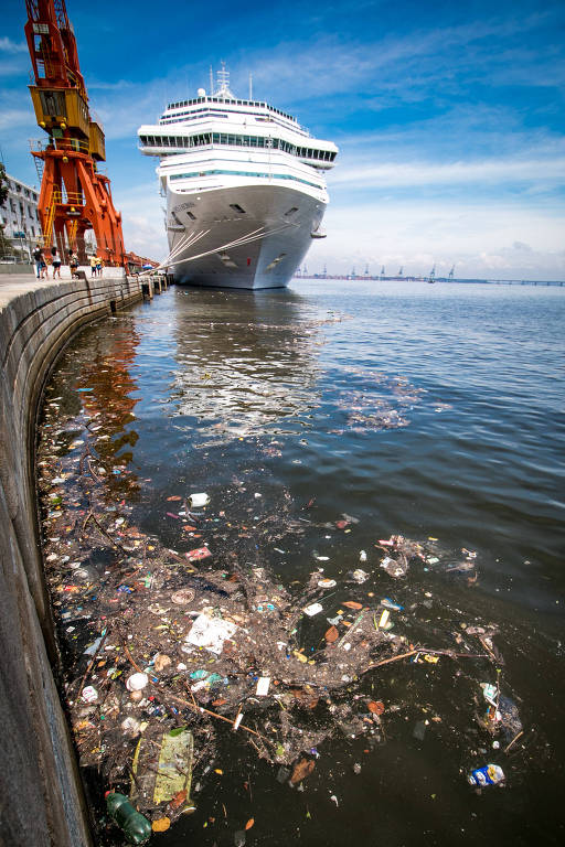 Lixo na baía de Guanabara, próximo ao Museu do Amanhã, área turística do Rio de Janeiro, com um navio de cruzeiros