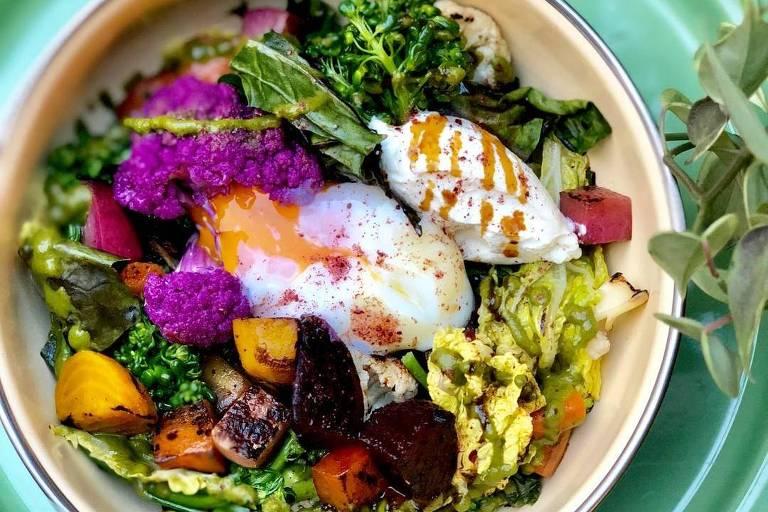 Salada Yotam servida no Isla Café tem verduras e legumes orgânicos tostados, zhoug, coalhada seca, ovo pochê e melaço de romã