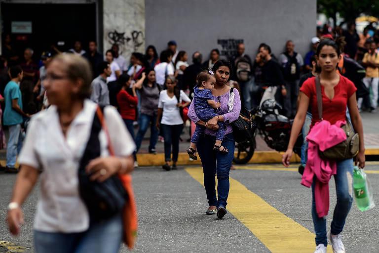 Pessoas na rua em Caracas durante apagão na cidade, o segundo em 24 horas