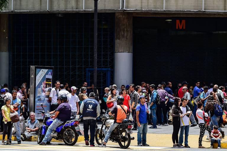 Pessoas aguardam do lado de fora de estação de metrô em Caracas após o apagão paralisar o transporte na cidade