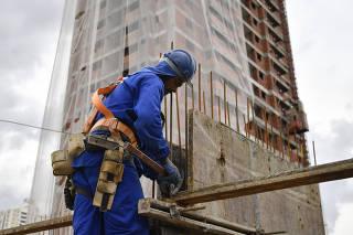 Operário trabalhando no na construção de edifício de alto padrão
