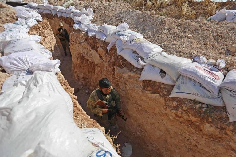Soldados rebeldes em trincheira se preparam para possível ofensiva do governo em Idlib, na Síria