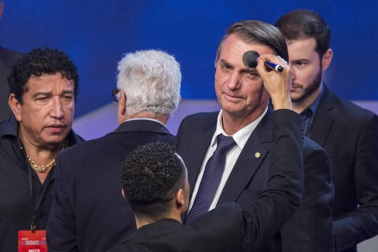 Jair Bolsonaro, vestido de terno, rodeado de assessores homens, também vestidos de terno, é maquiado por outro homem, que usa um pincel fofo de pó compacto. Todos estão num estúdio azul.