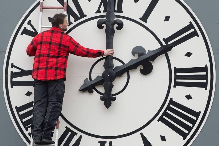 Técnico ajusa relógio em Dresden, na Alemanha; União Europeia quer acabar com mudança do horário de verão