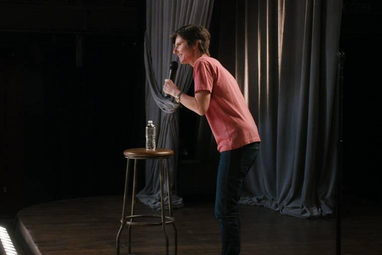 tig notaro com microfone num palco
