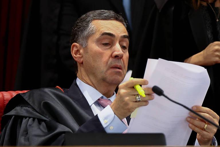 O ministro Luiz Roberto Barroso checa um documento durante a sessão extraordinária do TSE
