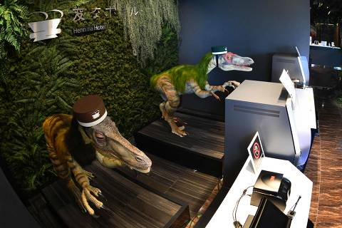 A pair of robot dinosaurs wearing bellboy hats welcome guests from the front desk at the Henn-na Hotel in Urayasu, suburban Tokyo on August 31, 2018. - The reception at the Henn-na Hotel east of Tokyo is eeriely quiet until customers near the robot dinosaurs manning front desk. Their sensors detect motion and they bellow: