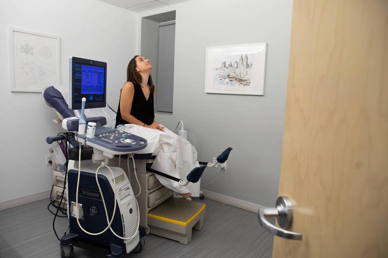 Jennifer Lannon sentada em uma cadeira de atendimento; a mulher olha para o teto do consultório, cercada de aparatos médicos