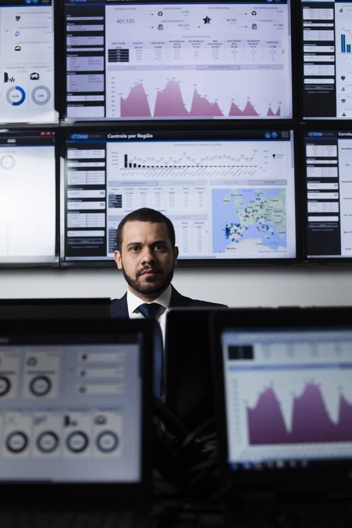 Homem de terno com telas à frente e atrás dele mostrando gráficos