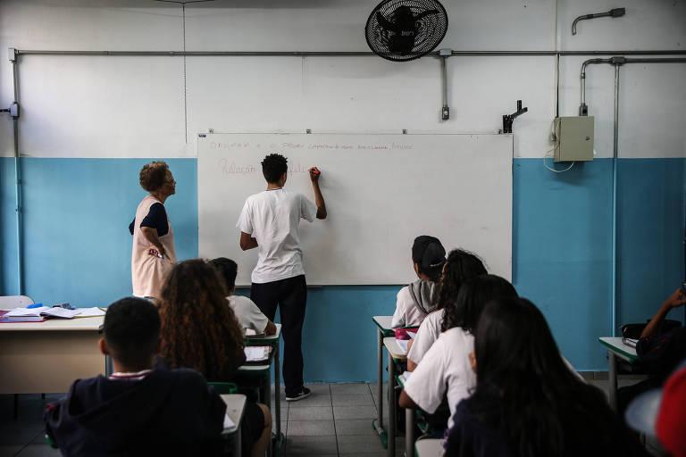 Sala de aula de escola, aluno escreve na losa
