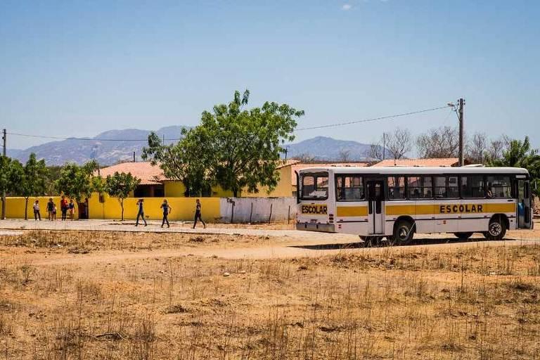 Muro da escola ao fundo, com alunos na frente e ônibus escolar