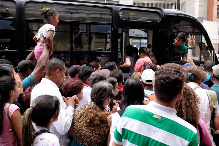 Pessoas se amontoam diante de porta aberta de ônibus