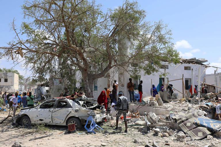 uma arvore no meio, diante dela um carro branco destruído, atrás, um predio de paredes brancas destroçado
