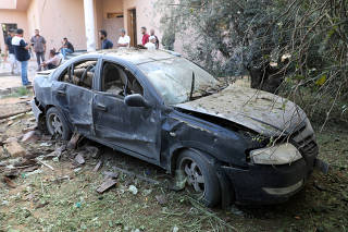 A damaged car is seen during clashes between rival factions in Tripoli, Libya