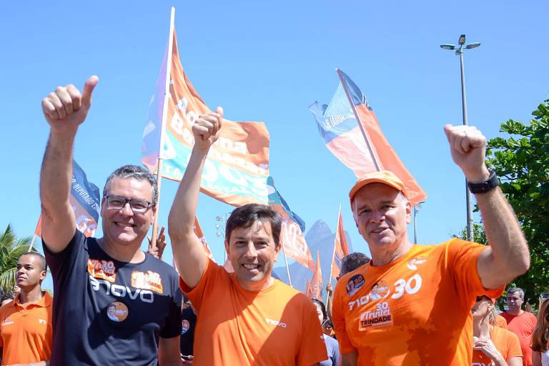 Homem de azul, à esquerda, e dois homens vestidos de laranja com os braços levantados fazendo sinal de joia