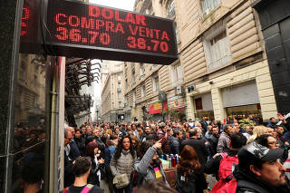 State workers gather in front of a currency exchange store during a protest against layoffs in Buenos Aires' financial district