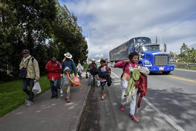 Migrantes venezuelanos andam em rodovia na Colômbia em direção ao Equador