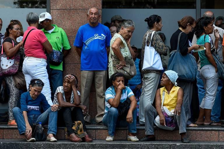 Venezuelanos fazem fila em banco para tentar sacar aposentadoria em Caracas; escassez de notas dificulta o saque