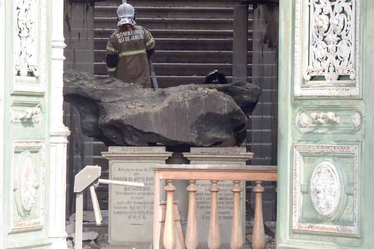 Bombeiro faz trabalho de rescaldo na entrada do Museu Nacional, onde fica o meteorito do Bendegó, após incêndio