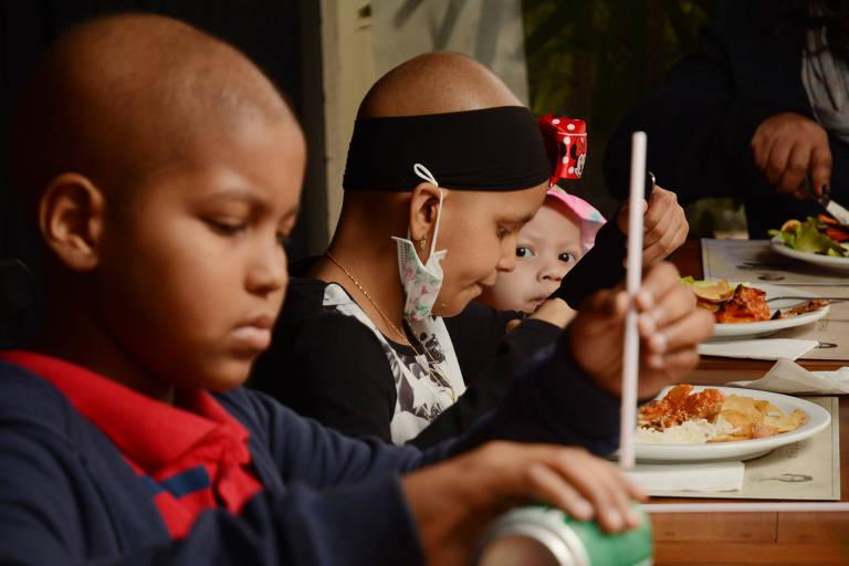 Imagem mostra crianças sem cabelo almoçando