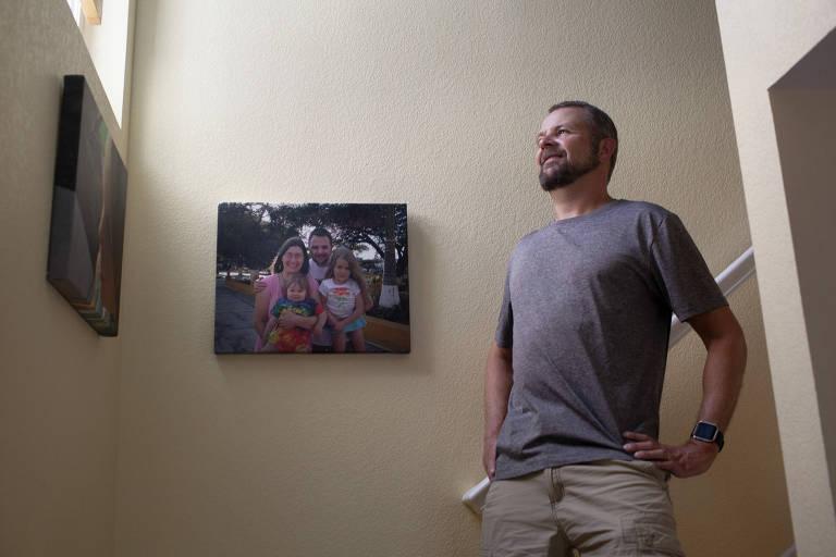 Carl Jensen coloca as mãos na cintura em frente a foto dele com a família