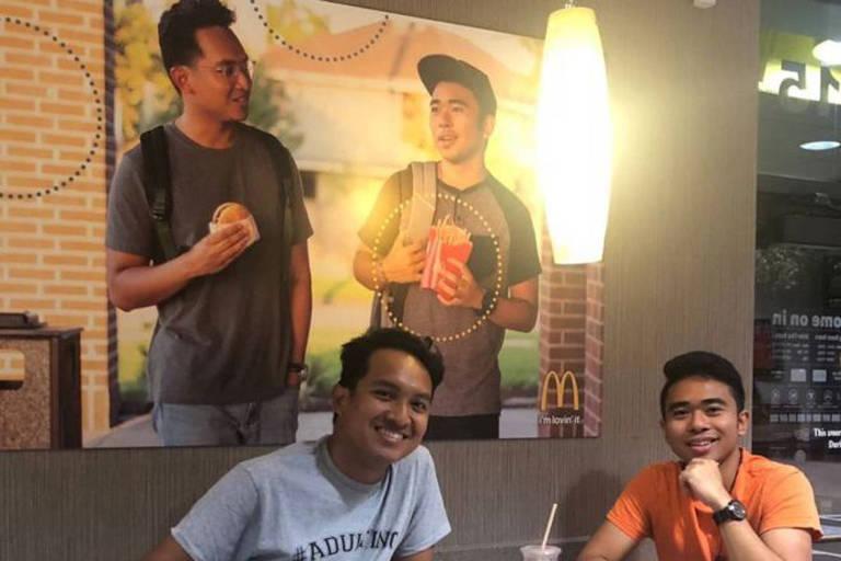 Jevh e Christian ao lado do pôster que produziram e penduraram no McDonald's