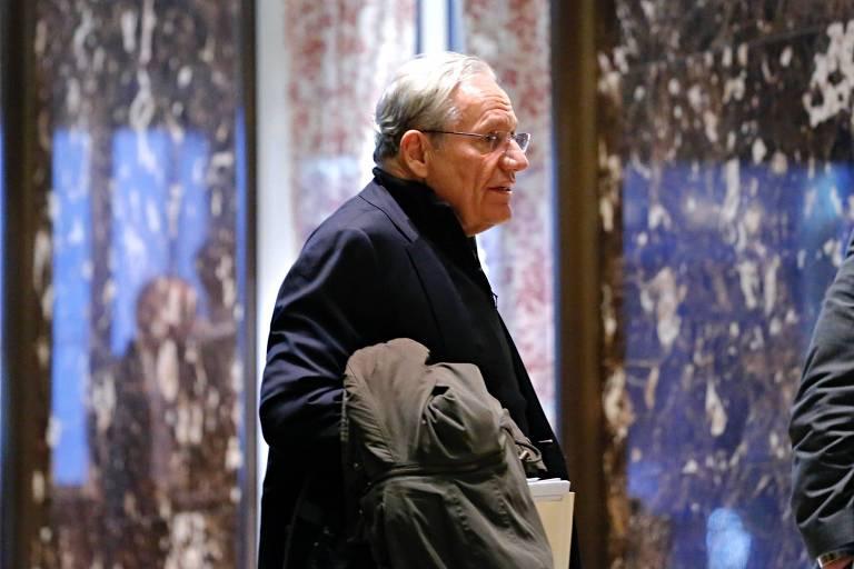 Bob Woodward é visto de perfil, vestindo terno e segurando um sobretudo, num saguão de mármore escuro
