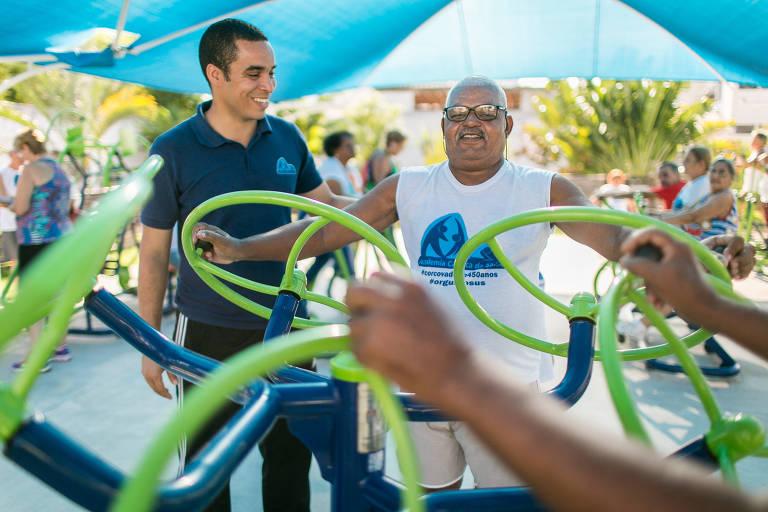 Homem faz exercícios junto a professor de educação física