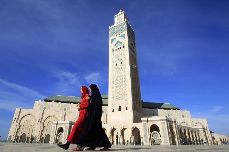 Duas mulheres com burca passam em frente a mesquita em dia ensolarado