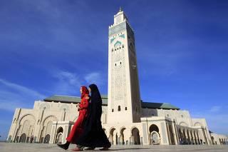 Moroccan women walk past the Hassan II mosque in Casablanca