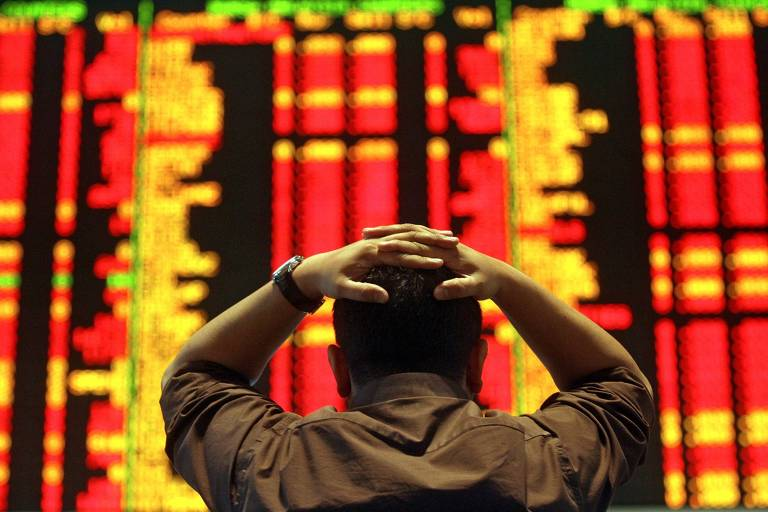 Investidor observa painel em dia de queda dos mercados