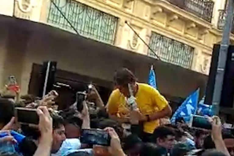Bolsonaro, de camiseta amarela, leva mão ao abdômen após levar facada em Juiz de Fora