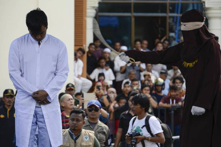 Foto de julho de 2018 mostra policial se preparando para chicotear um homem acusado de ter feito sexo com outro homem na província de Aceh, na Indonésia, onde a homossexualidade é crime