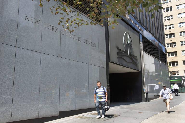 Duas pessoas passam diante da fachada de granito da Arquidiocese de Nova York em um dia de sol