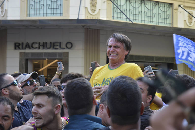Presidential candidate Jair Bolsonaro grimaces right after being stabbed in the stomach during a campaign rally