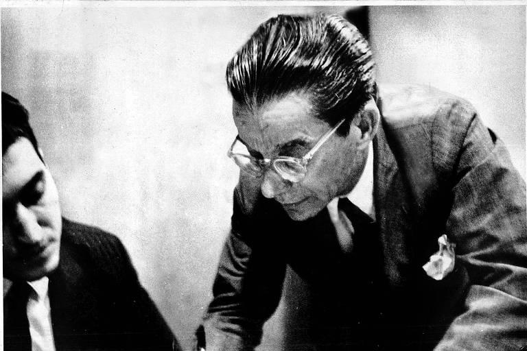 homem de cabelos penteados para trás, vestindo terno, se debruça sobre mesa para ler algo. foto em preto e branco bastante antiga