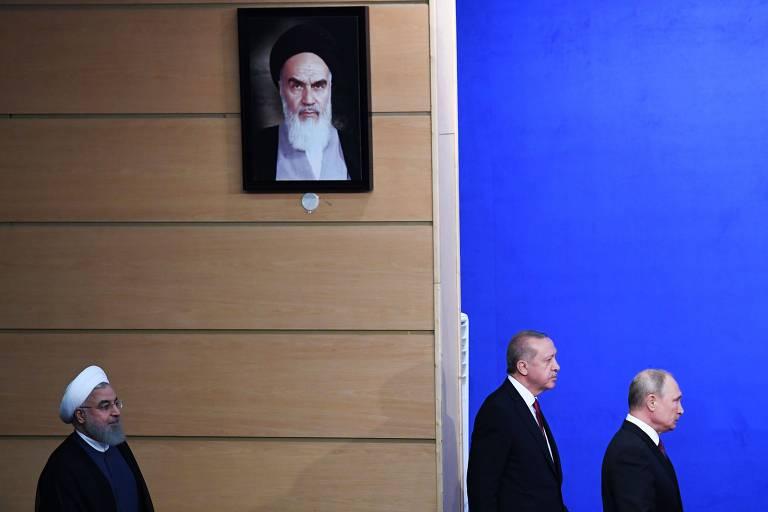 Os presidentes do Irã, Hassan Rowhani, da Turquia, Recep Tayyip Erdogan, e da Rússia, Vladimir Putin (da esq. para a dir.) passam por retrato do aiatolá Khomeini antes de entrevista coletiva sobre a cúpula
