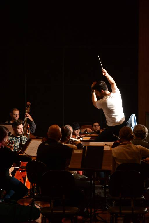Maestro rege orquestra durante ensaio