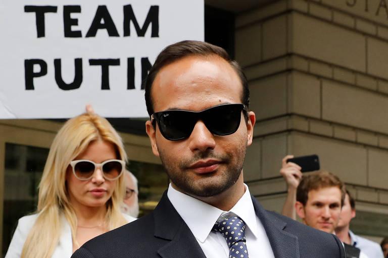 De óculos escuros, Papadopoulos olha para a câmera, seguido de sua mulher, também de óculos.