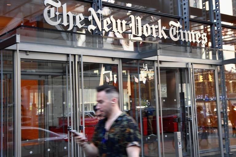 Homem usa smartphone em frente à sede do jornal The New York Times