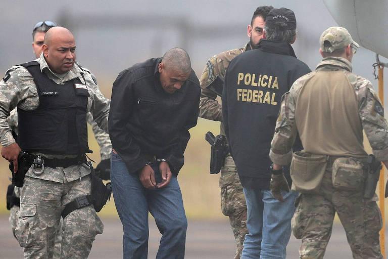 Adelio Bispo de Oliveira aparece, vestido de preto, algemado e caminhando de cabeça encolhida, rodeado por agentes da polícia federal fardados