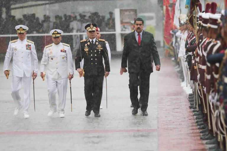 O ditador Nicolás Maduro usa gravata vermelha ao lado de chefes das Forças Armadas da Venezuela fardados em desfile em Caracas durante chuva