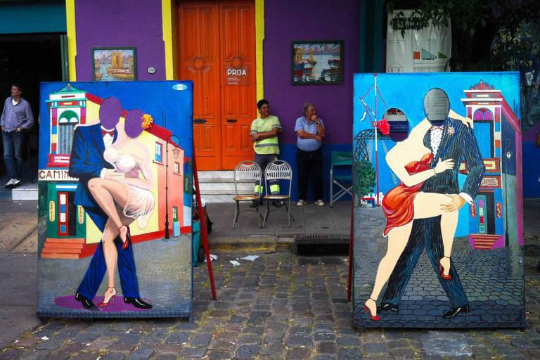 Placas de madeira com lugar para duas pessoas encaixarem a cabeça para tirar uma foto. As placas são pintadas com imagens de dois casais dançando tango