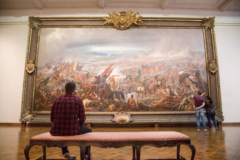 """Visitante diante da monumental tela """"A Batalha do Avaí"""", de Pedro Américo"""