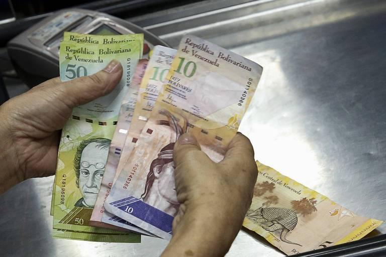 Caixa conta notas de bolívares em mercado, em Caracas