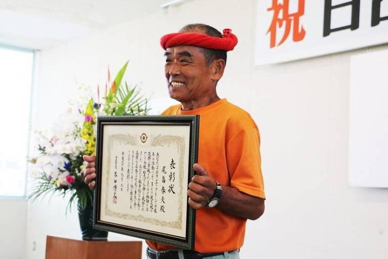 Conhecido como 'supervoluntário', Haruo Obata segura placa de homenagem