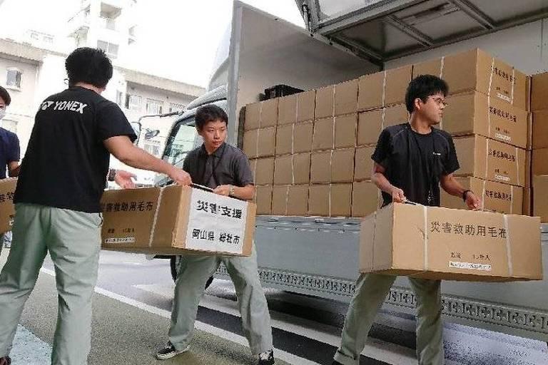 Voluntários da cidade de Soja carregam caixas com doações