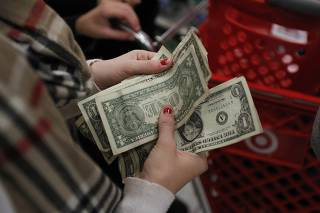 A customer counts her money while waiting in line to check out at a Target store on the shopping day dubbed