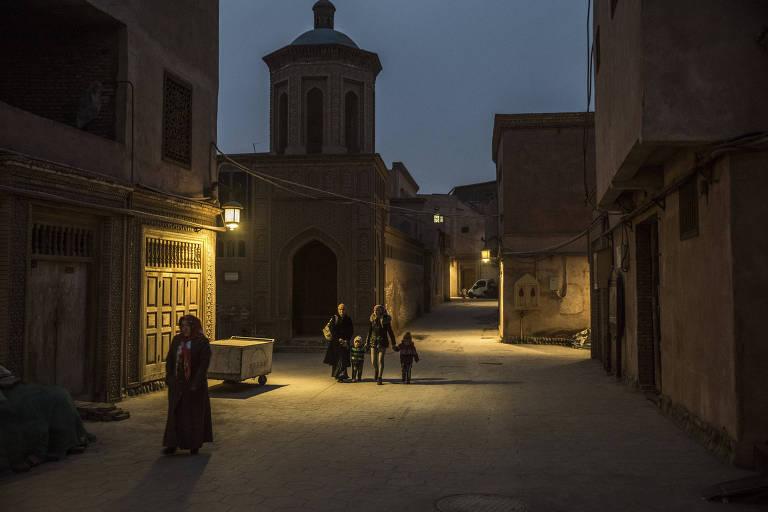 Pessoas passam por uma rua escura ao lado de uma mesquita. Duas mulheres usam o véu islâmico.