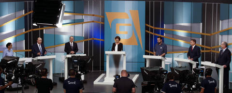 Brazilian presidential candidates (L to R) Marina Silva (Rede), Henrique Meirelles (MDB), Geraldo Alckmin (PSDB), Guilherme Boulos (PSOL), Alvaro Dias (Podemos) and Ciro Gomes (PDT) stand next to journalist and moderator Maria Lidia (C) during the third presidential debate ahead of the October 7 general election, at Gazeta TV television network in Sao Paulo, Brazil, on August 17, 2018. (Photo by Miguel SCHINCARIOL / AFP)